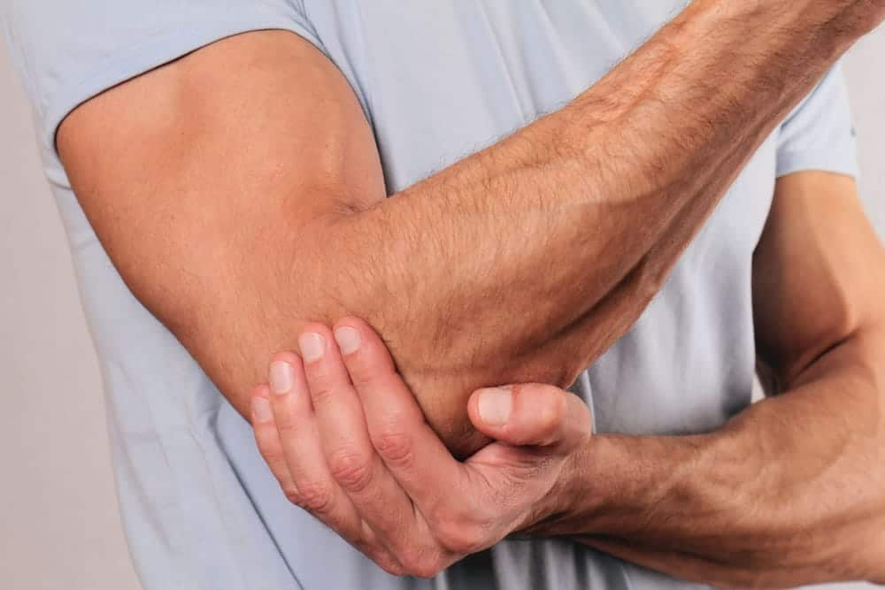 man holding his elbow due to arthritis pain
