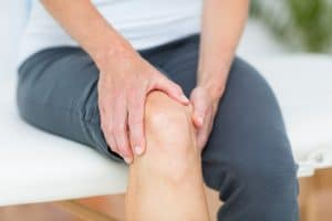 Knee Pain is felt by patient in fort wayne as he holds knee