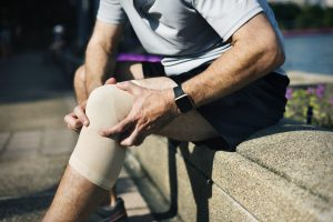 Man holding his knee in pain that is wrapped in a bandage