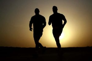 Runners with sun in background experiencing foot pain