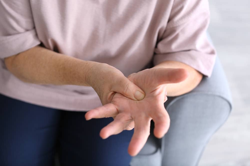 Elderly lady holding her hand due too arthritis pain