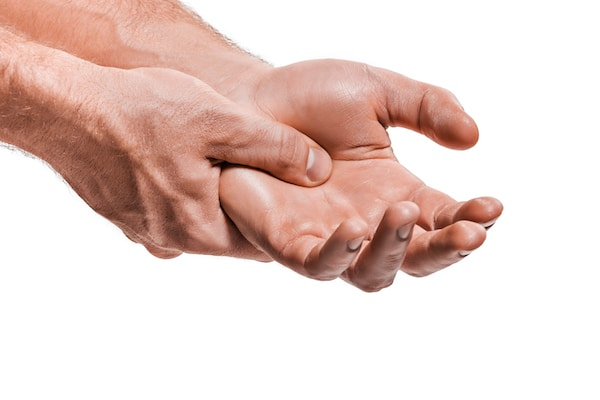 man holding his hand and wrist due to pain