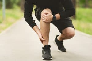 male runner holding his right knee due to pain