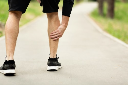 man holding his calf muscle due to a muscle tear