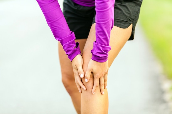 woman holding her knee due to pain