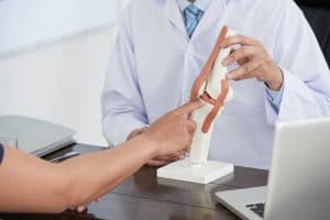 doctor holding a knee muscle tear figure