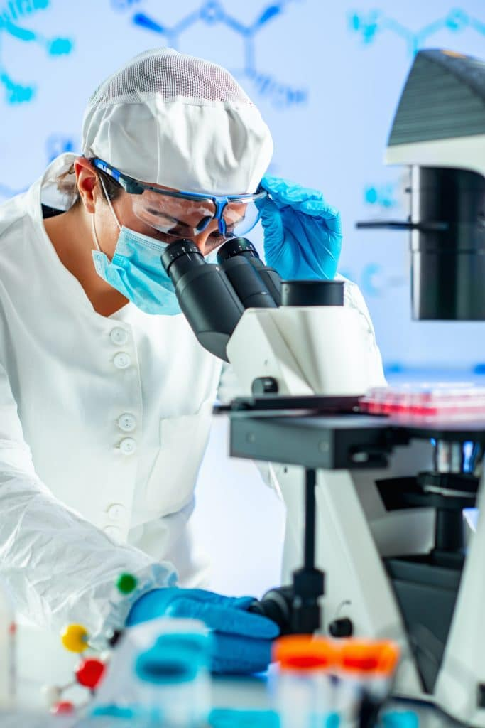 scientist looking throug a microscope at stem cells