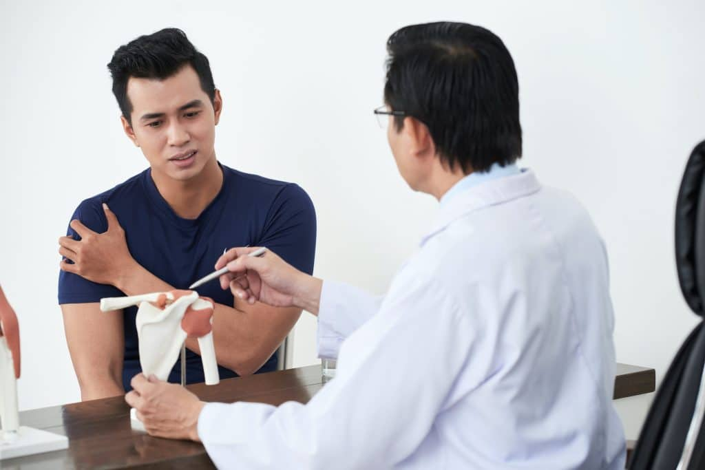 young male talking to the doctor about his shoulder pain