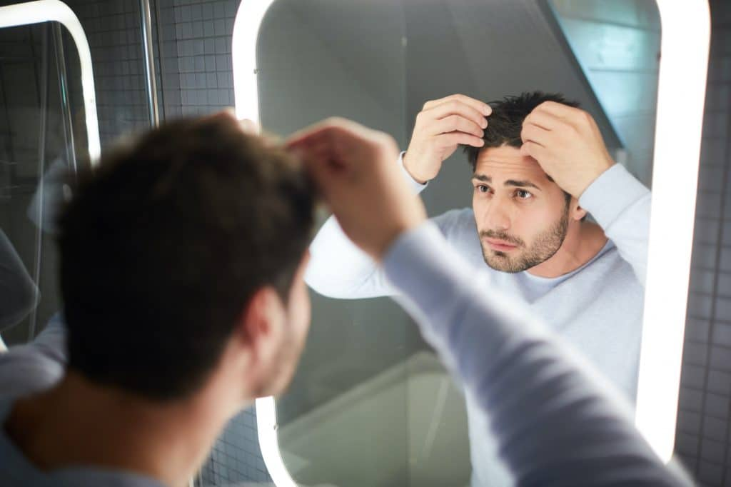 young man looking in the mirror at his hair loss
