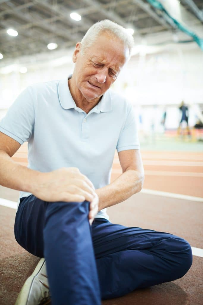 older man holding his knee due pain pain