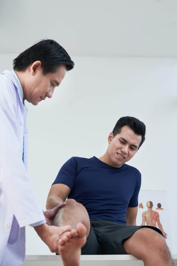 young male visiting the doctor due to his knee pain