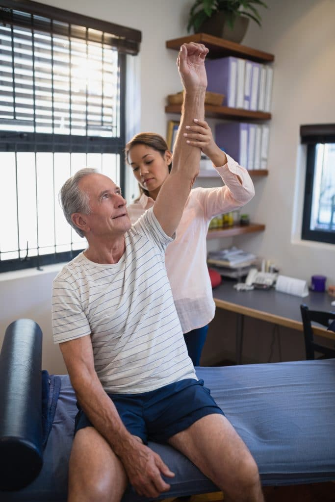 doctor examining male patients shoulder mobility